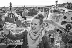 Mujer del viajero en el parque de Guell que toma el selfie con el teléfono móvil Foto de archivo libre de regalías