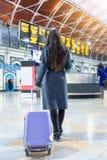Mujer del viajero en una estación de tren ocupada que mira las pantallas del calendario fotografía de archivo libre de regalías