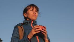 Mujer del viajero que bebe té caliente y que mira puesta del sol contra el cielo azul turista de la muchacha, soportes encima de  almacen de video