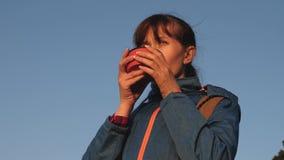 Mujer del viajero que bebe t? caliente y que mira puesta del sol contra el cielo azul turista de la muchacha, soportes encima de  almacen de video