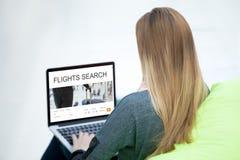 Mujer del viajero que busca para un vuelo en el ordenador portátil Fotos de archivo libres de regalías