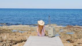 Mujer del viajero que se sienta en su maleta en la playa metrajes