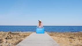 Mujer del viajero que se sienta en su maleta en la playa almacen de metraje de vídeo
