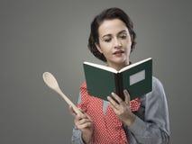 Mujer del vintage con el libro de cocina Fotografía de archivo libre de regalías