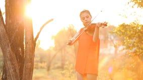 Mujer del violinista en la puesta del sol