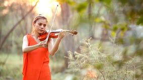Mujer del violinista en la puesta del sol almacen de metraje de vídeo