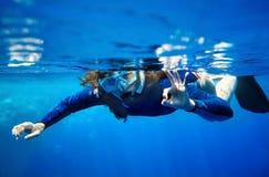 Mujer del zambullidor de equipo de submarinismo en agua azul. Fotografía de archivo libre de regalías