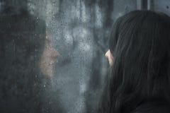 Mujer delante de la ventana lluviosa foto de archivo