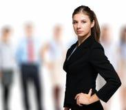 Mujer delante de un grupo de hombres de negocios Foto de archivo libre de regalías