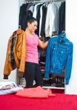 Mujer delante del armario por completo de la ropa Imagen de archivo libre de regalías