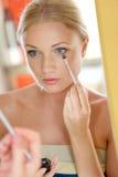 Mujer delante del espejo que pone maquillaje Imagenes de archivo