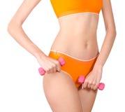 Mujer delgada apta que ejercita con pesas de gimnasia Imagen de archivo libre de regalías