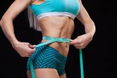 Mujer delgada atlética que mide su cintura por la cinta de la medida después de una dieta sobre fondo negro Imagenes de archivo