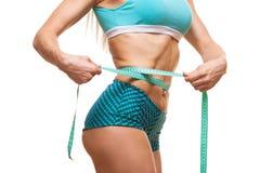 Mujer delgada atlética que mide su cintura por la cinta de la medida después de una dieta sobre fondo negro Imágenes de archivo libres de regalías