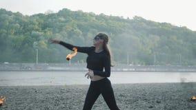 Mujer delgada confiada en el baile de la máscara, realizando una demostración con la bola de fuego que se coloca en el riverbank  almacen de video