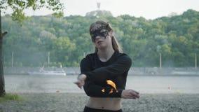 Mujer delgada confiada en el baile de la máscara, realizando una demostración con la bola de fuego que se coloca en el riverbank  almacen de metraje de vídeo