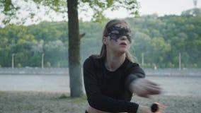 Mujer delgada en el baile de la máscara, realizando una demostración con la bola de fuego que se coloca en el riverbank Demostrac almacen de metraje de vídeo