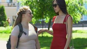 Mujer delgada en el vestido rojo que apoya al amigo femenino gordo en parque del campus metrajes