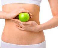 Mujer delgada en la ropa interior blanca con la manzana verde en Fotos de archivo libres de regalías