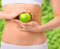 Mujer delgada en la ropa interior blanca con la manzana verde en Fotografía de archivo libre de regalías