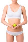 Mujer delgada en la ropa interior blanca con la manzana verde en Imágenes de archivo libres de regalías