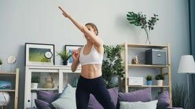 Mujer delgada en ropa de los deportes que ejercita en casa aumentando los brazos y poniéndose en cuclillas almacen de metraje de vídeo