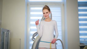 Mujer delgada flaca que mide su volumen de la cintura con la cinta almacen de metraje de vídeo