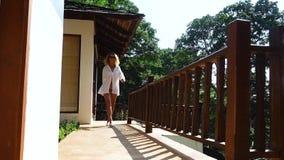 Mujer delgada hermosa en gafas de sol y la camisa blanca que camina en la terraza en un día de verano soleado caliente metrajes