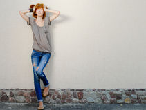 Mujer delgada hermosa joven que se coloca cerca de la pared gris Foto de archivo