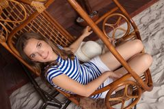 Mujer delgada hermosa que se sienta en un oscilación de madera en la playa fotos de archivo libres de regalías