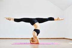 Mujer delgada joven del gimnasta en la ropa de los deportes que se coloca al revés Imágenes de archivo libres de regalías