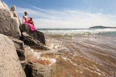 Mujer delgada joven en la orilla rocosa del mar en un traje de natación rosado y una tela rosada que agitan en el viento Fotos de archivo