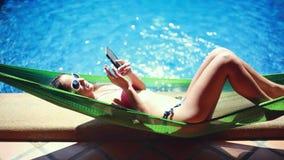 Mujer delgada joven hermosa en bikini que coloca en hamaca mientras que usa el teléfono por la piscina en la sol hermosa almacen de video