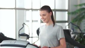 Mujer delgada joven que ejercita en el gimnasio almacen de metraje de vídeo