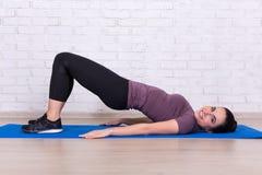 Mujer delgada joven que hace los ejercicios para los músculos abdominales Fotos de archivo