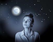 Mujer delgada joven que mira la Luna Llena Imágenes de archivo libres de regalías