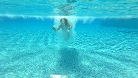 Mujer delgada joven que salta en la piscina y que nada debajo del agua metrajes