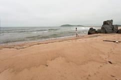 Mujer delgada joven que se coloca en una costa abandonada Imagenes de archivo
