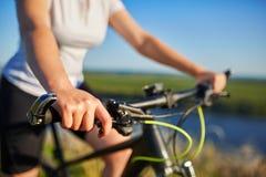Mujer delgada joven que se sienta en la bicicleta, sosteniendo los manillares con las manos Mujer en la iluminación de la puesta  Imagen de archivo