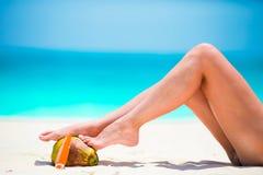 Mujer delgada que aplica la protección solar en sus piernas, sentándose en la playa arenosa con el fondo del mar Foto de archivo libre de regalías