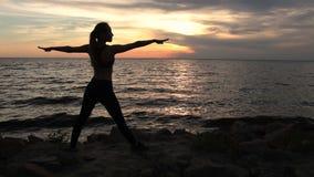Mujer delgada que ejercita actitud del guerrero de la yoga en la playa almacen de metraje de vídeo