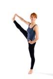Mujer delgada que hace la pierna que estira ejercicio de la yoga imagen de archivo