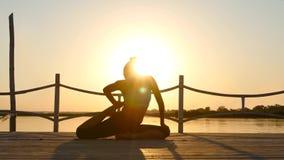 Mujer delgada que hace yoga sobre el sol anaranjado almacen de video