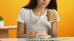 Mujer delgada snacking en el buñuelo esmaltado delicioso y la bebida caliente de consumición almacen de video