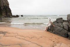 Mujer delgada sola en una playa abandonada en el fondo de piedras grandes y de un cielo nublado Imágenes de archivo libres de regalías