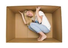 Mujer dentro de una caja de cartón Foto de archivo libre de regalías