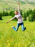 Mujer deportiva activa que salta al aire libre Imagen de archivo