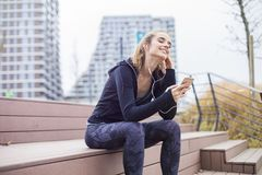 Mujer deportiva apta de los jóvenes que descansa y escuchar música en el teléfono móvil foto de archivo