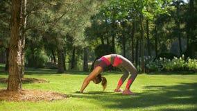 Mujer deportiva apta que hace ejercicio del backbend al aire libre metrajes