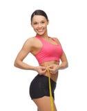 Mujer deportiva con la cinta métrica Fotos de archivo